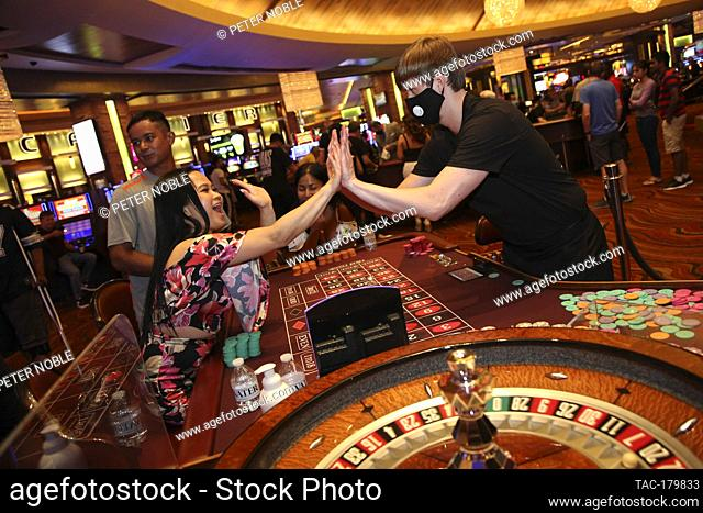 Las Vegas, NV - June 4, 2020: A Player High Fives the dealer during the Grand Re-Opening of Red Rock Casino Resort & Spa at 12:01 AM on June 4