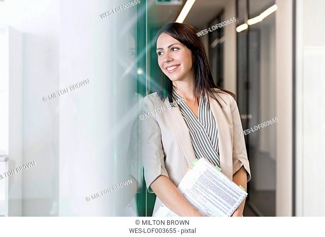 Young businesswoman standing in corridor, holding files