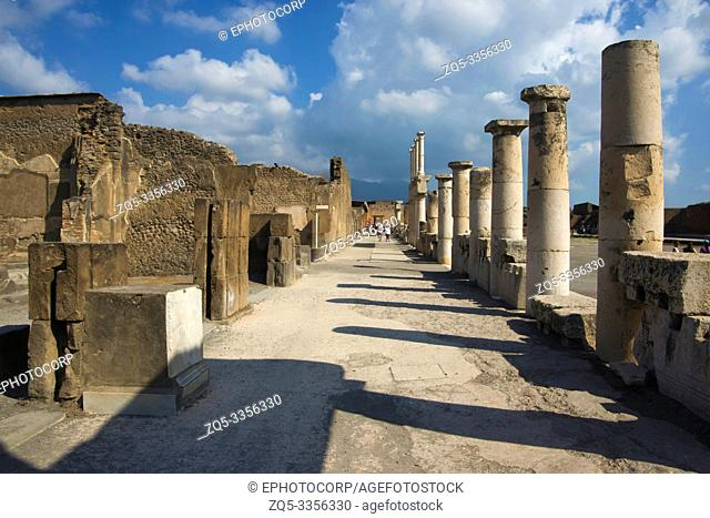 POMPEII, ITALY, July 2018, Tourist at ruins showing tall pillars, rooms and the street