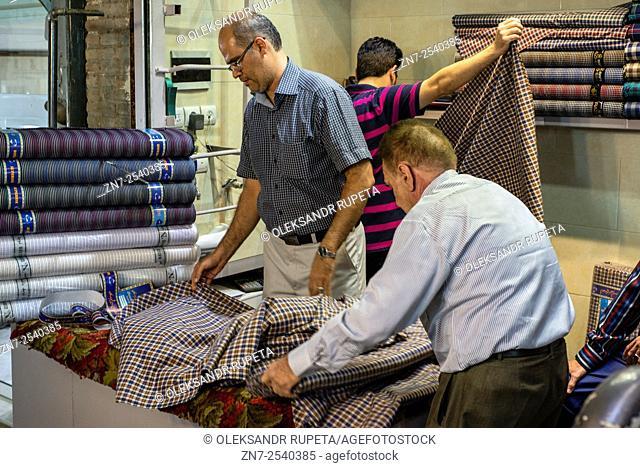 Workers fold textile in the shop in Grand bazaar in Tehran, Iran