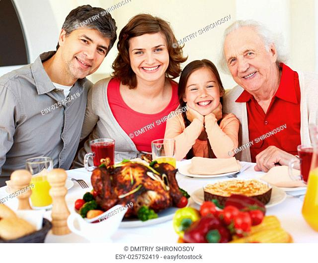 Happy family sitting at celebration table on Thanksgiving Day