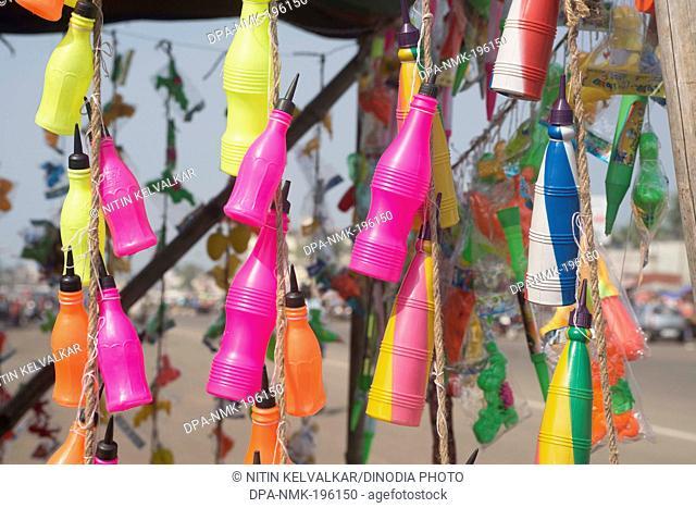 Plastic bottle pichkari hanging outside stall, puri, orissa, india, asia