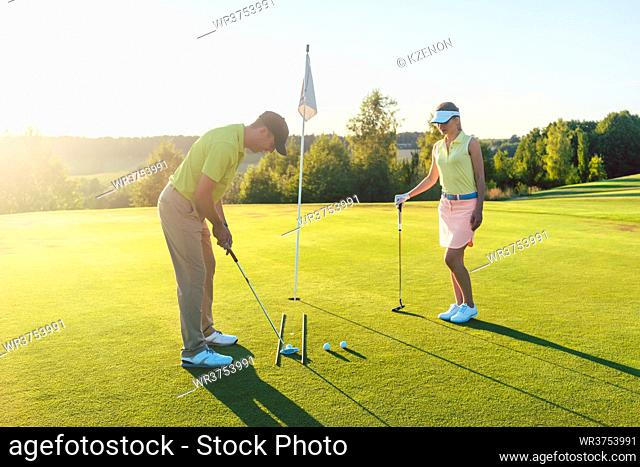 Full length side view of a man ready to hit the golf ball into the hole while exercising the short shot, with his game partner in a modern country club in...