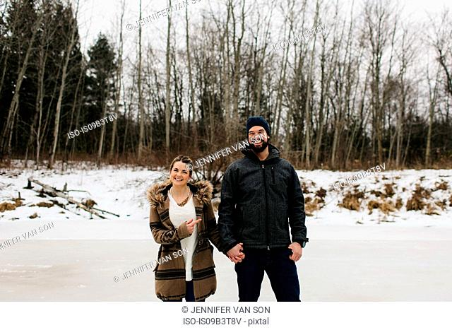 Happy couple on frozen lake, Whitby, Ontario, Canada
