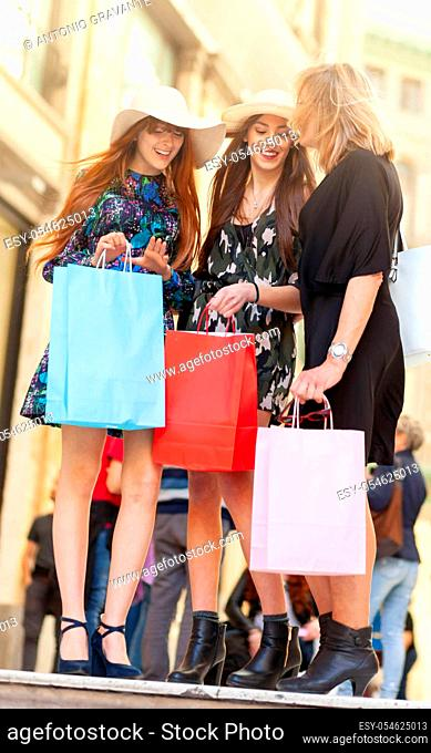 Three friends or mum with daughters go shopping