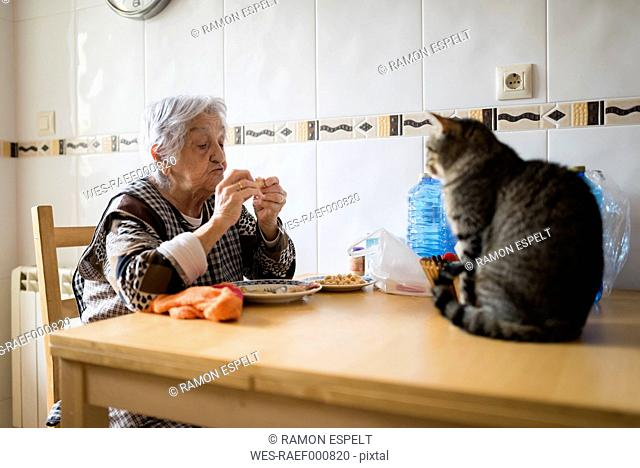 Senior woman eating while the cat watching her