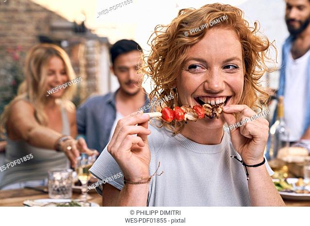 Young woman eating meat skewer at a backyard patry with friends