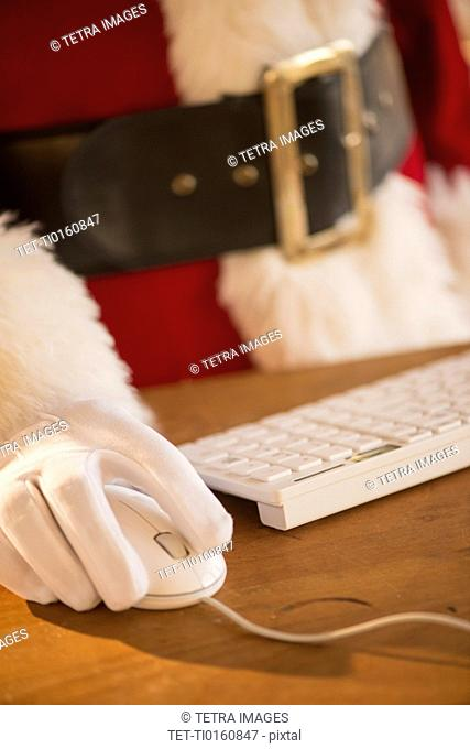 Close-up of santa claus using computer