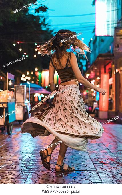 Thailand, Bangkok, young woman in the city dancing on the street at night