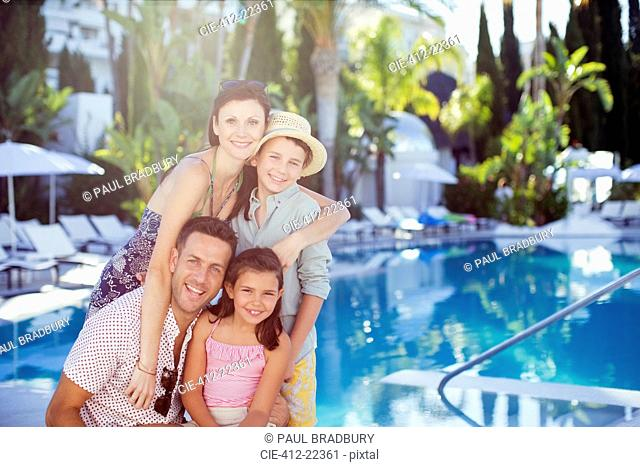 Portrait of happy family with son and daughter by swimming pool