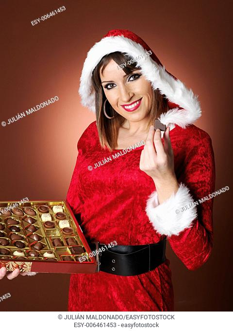 Young woman dressed in Mama Claus with some chocolates