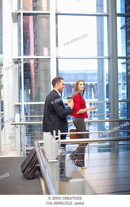 Mid adult businesswoman and colleague on conference centre walkway