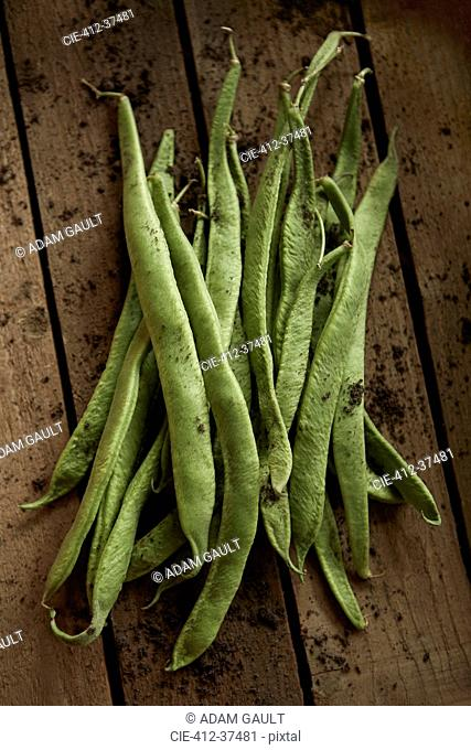 Still life close up fresh, organic, healthy, rustic, dirty green bean pods on wood