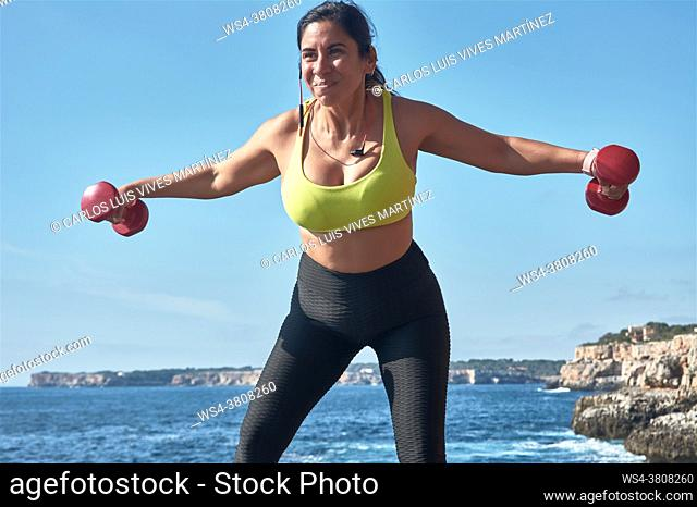Latin woman, middle-aged, wearing sportswear, training, doing physical exercises, plank, sit-ups, climber's step, burning calories, keeping fit