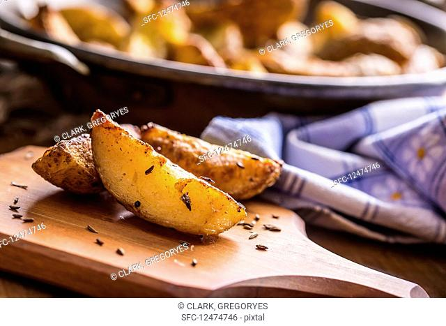 Roasted potato wedges with carawaYes seeds (close up)