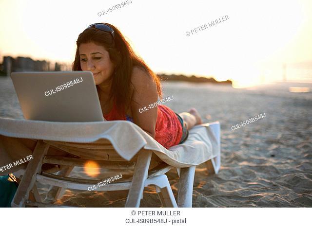 Mature woman lying on beach sun lounger looking at laptop, Dubai, United Arab Emirates