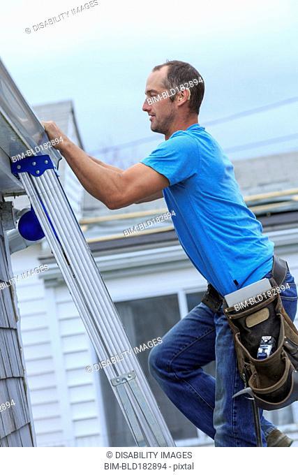 Deaf Caucasian roofer climbing ladder