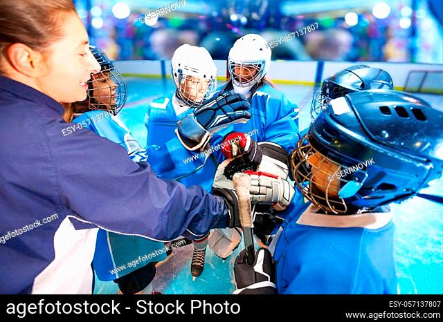 Close-up portrait of female coach and ice hockey team putting hands in huddle before the game, in junior league