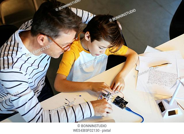 Father and son assembling a construction kit with wind turbine model