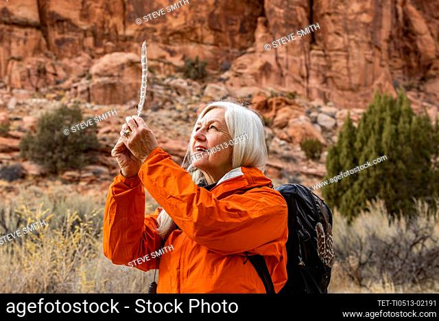 USA, Utah, Escalante, Woman looking at feather while hiking in Grand Staircase-Escalante National Monument