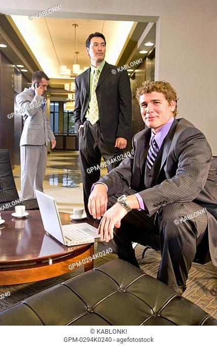 Portrait of multi-ethnic businessmen with laptop in modern lobby