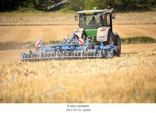 Rear View Of Tractor Ploughing Field Using Disc Plough