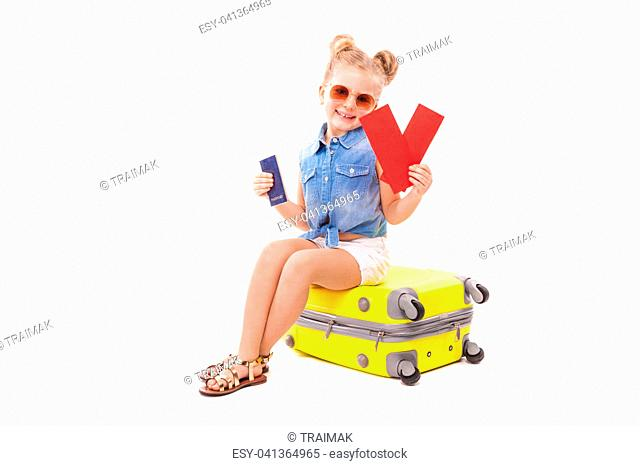 Isolated on white, little caucasian blonde girl in blue jeans shirt, white shorts, sunglasses and sandals sit on the yellow suitcase