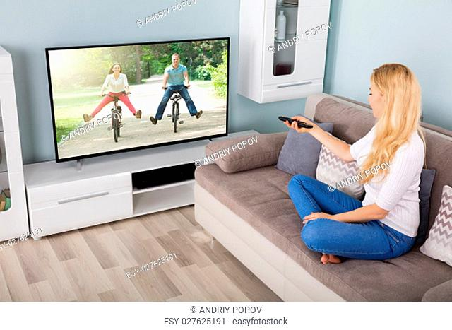 Young Woman Sitting On Couch Watching Movie On Television At Home