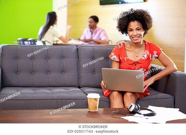 Woman Taking A Break Working On Sofa In Design Studio