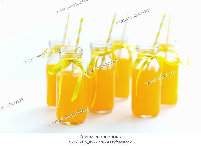 orange juice in glass bottles with paper straws