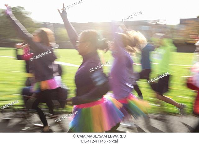 Enthusiastic runners in tutus running at charity run in sunny park