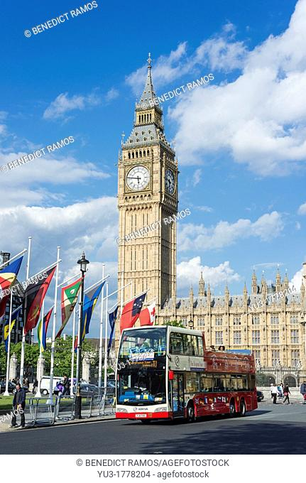 Open top tourist bus passes in front of Big Ben and the Houses of Parliament, London, England