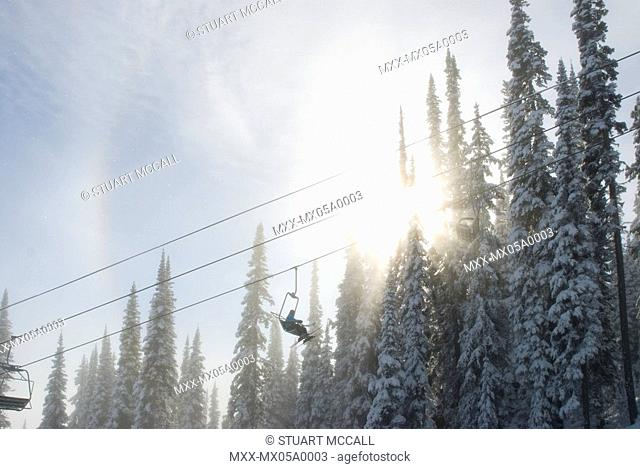 Canada, BC, Sun Peaks Resort. Chairlift moving through the snow covered trees. Early winter at ski resort in BC's southern interior