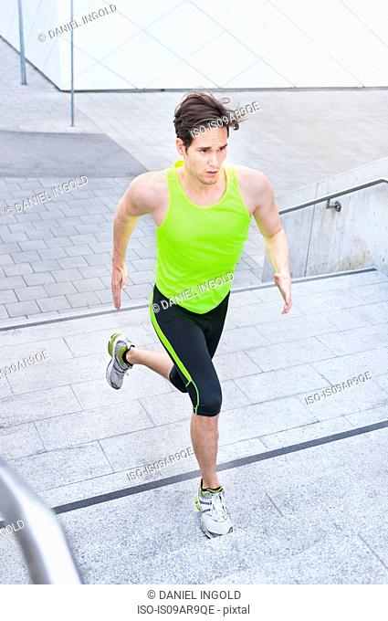 Portrait of mid adult man running up steps