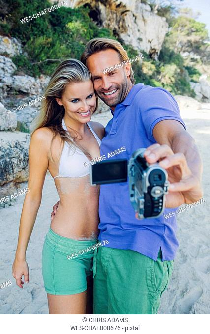 Couple filming themselves with a camcorder at the beach