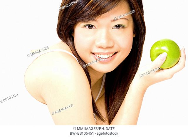 A pretty young asian woman holds an apple