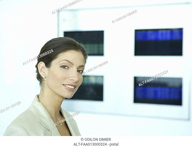 Woman standing in front of airport departure board