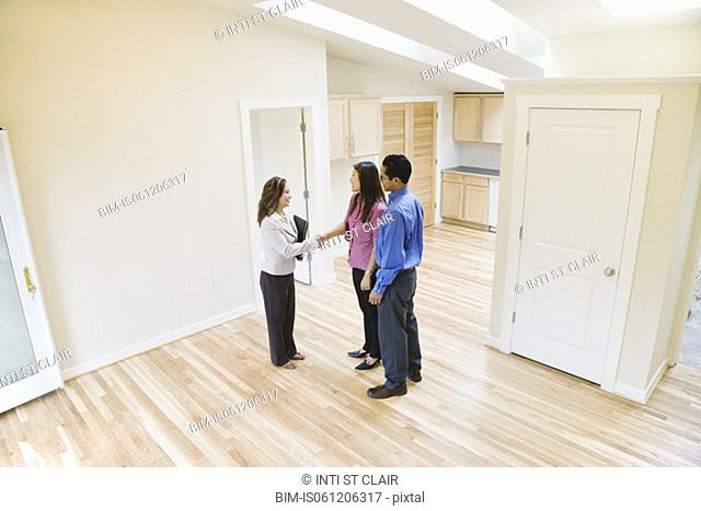 Asian couple shaking hands with real estate agent in new house