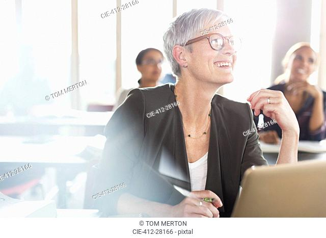 Smiling senior woman at laptop in adult education classroom