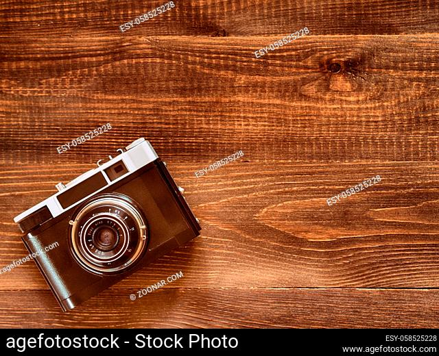 top view image of vintage old camera on wooden table background. Flat lay