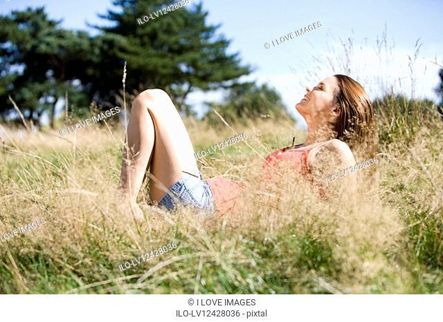 A young woman lying on the grass, enjoying the sunshine