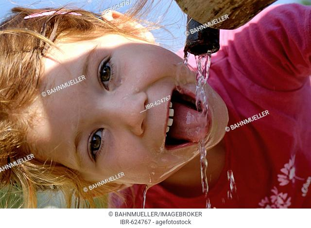 Child drinking natural water from a fountain