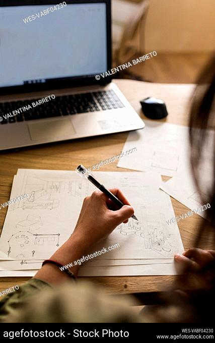 Female carpenter with laptop making design on paper at desk in industry