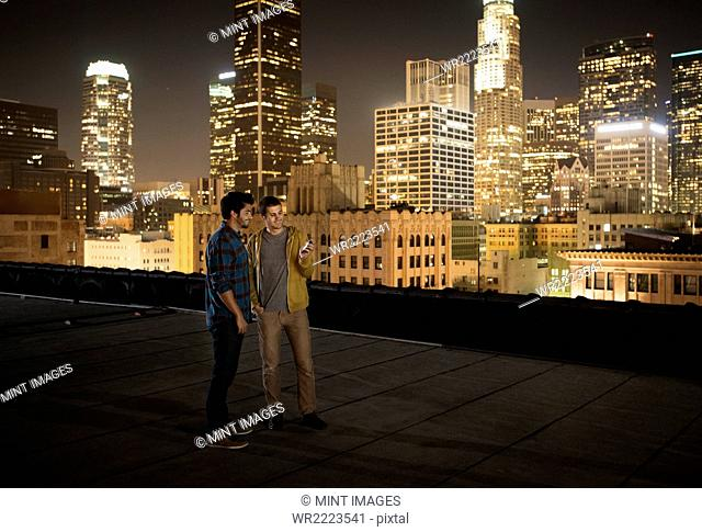 Two men on a rooftop overlooking Los Angeles at night, looking at a smart phone