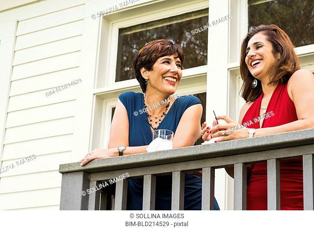Hispanic women in formal wear drinking cocktails on balcony