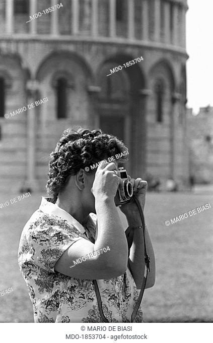 A woman photographing the monuments of piazza del Duomo. In the background, the Baptistry of St. John. Pisa, 1963