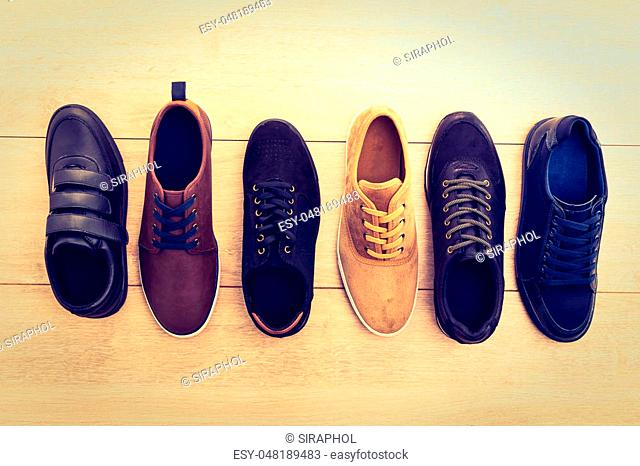 Beautiful many leather shoes for men on wooden background - Vintage light Filter processing