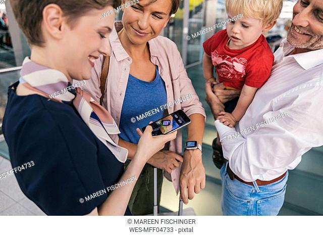 Airline employee scanning QR codes of passengers with smartwatch at the airport