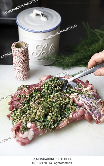 Raw lamb shoulder being spread with herb paste