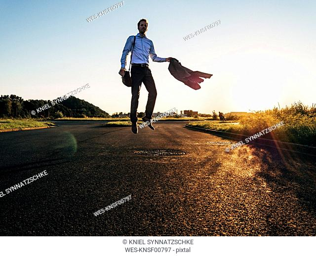 Businessman jumping on rural road